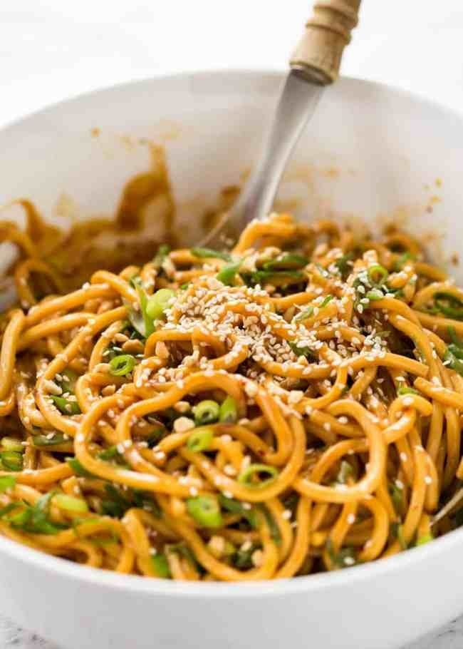 A bowl of peanut sesame noodles with sesame seeds and scallions.