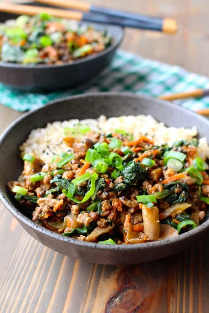 Two bowls of pork and vegetable stir fry over rice.