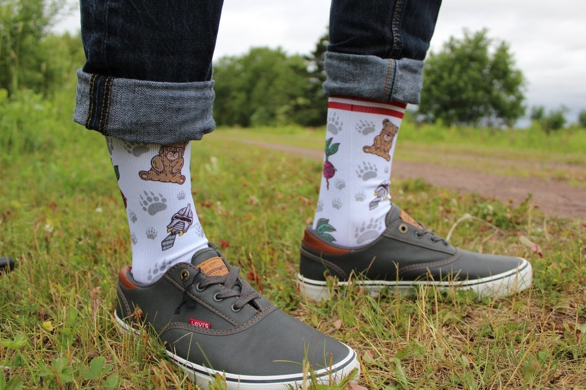 A person wearing the socks with bears, aliens, and beets on them