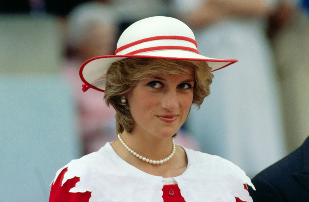 Princess Diana wearing a dress with a decorative sailor collar and matching hat along with a pearl necklace and earrings