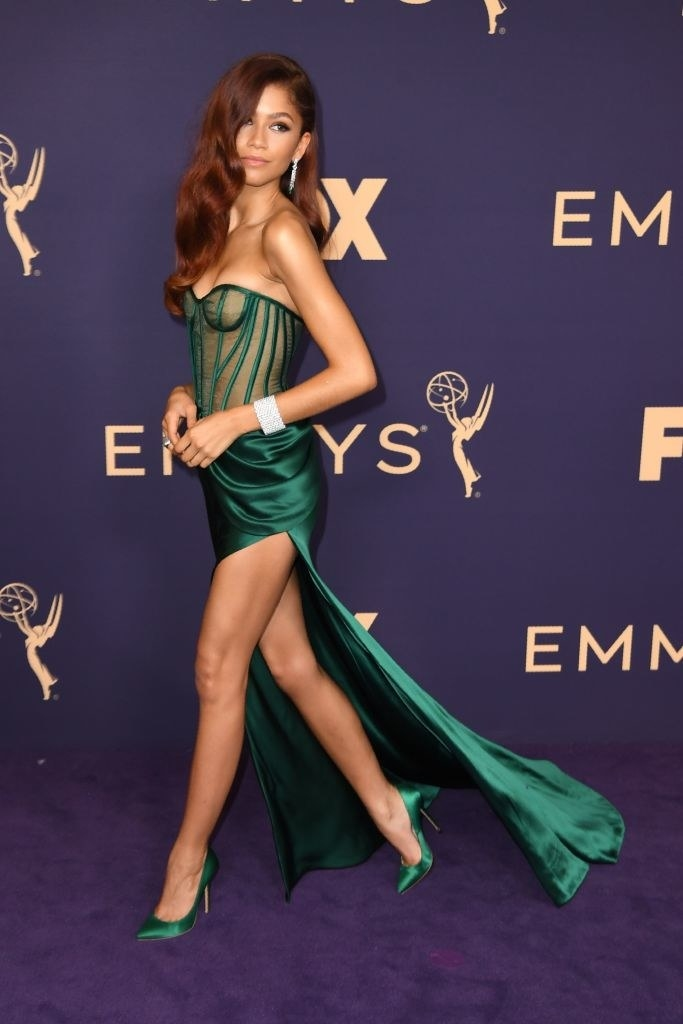 Zendaya walking across the Emmys red carpet in a deep green gown with a slit up the side of the leg.