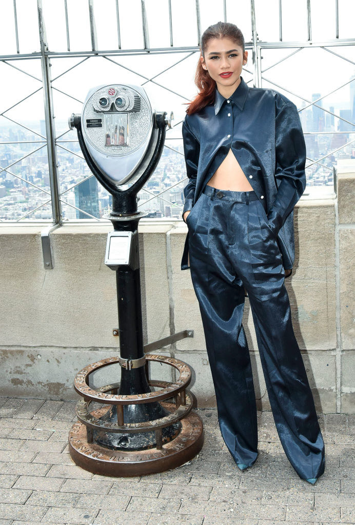 Zendaya standing on top of the empire state building wearing a silk button down shirt, with only the top three buttons secured. She's wearing matching pants.