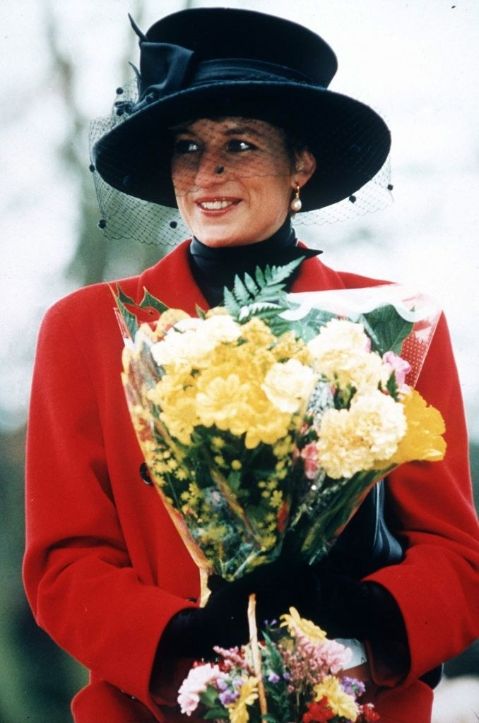 Princess Diana wearing a long winter coat, gloves, and a hat with lace netting covering her face