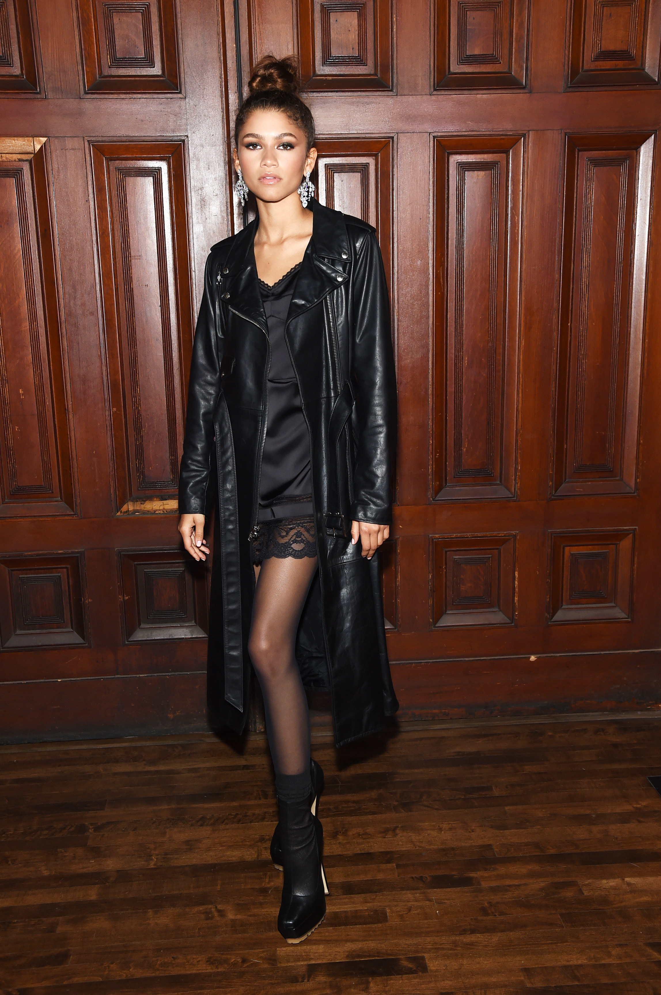 Zendaya posing wearing hair in a tight topknot, with a slip dress, knee-length leather jacket and boots.