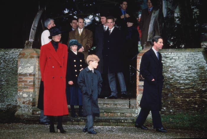 Princess Diana, wearing a long winter coat and hat, walks with a young Prince Harry and Prince Charles