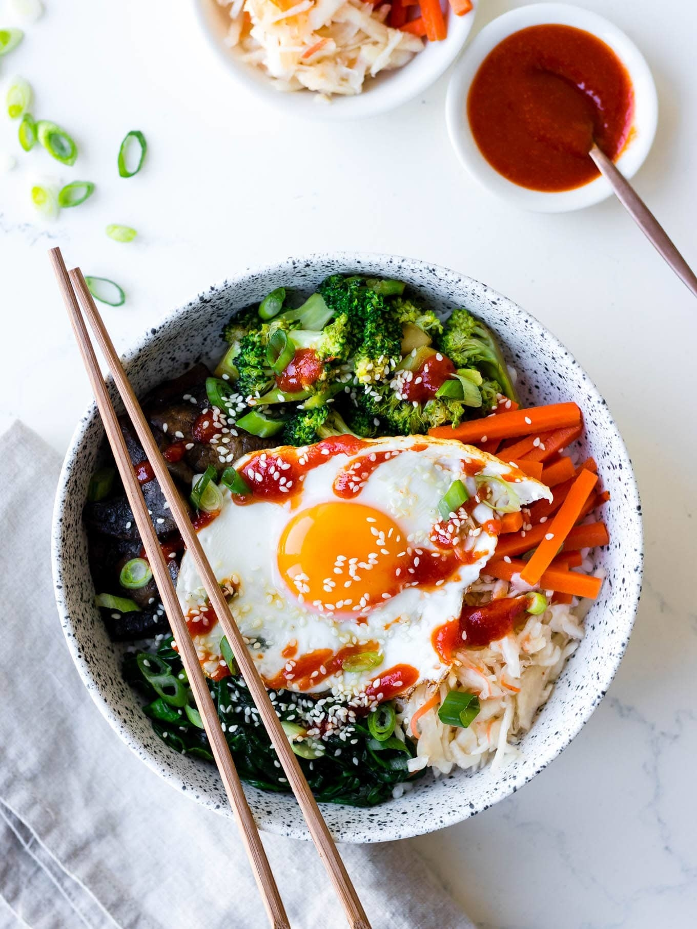 Korean rice bowls with greens, carrots, and fried egg.