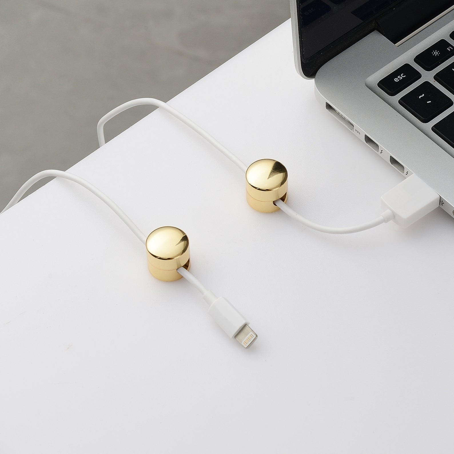 A set of two gold finished round cable organizers installed on a desk with a charger wire running through them