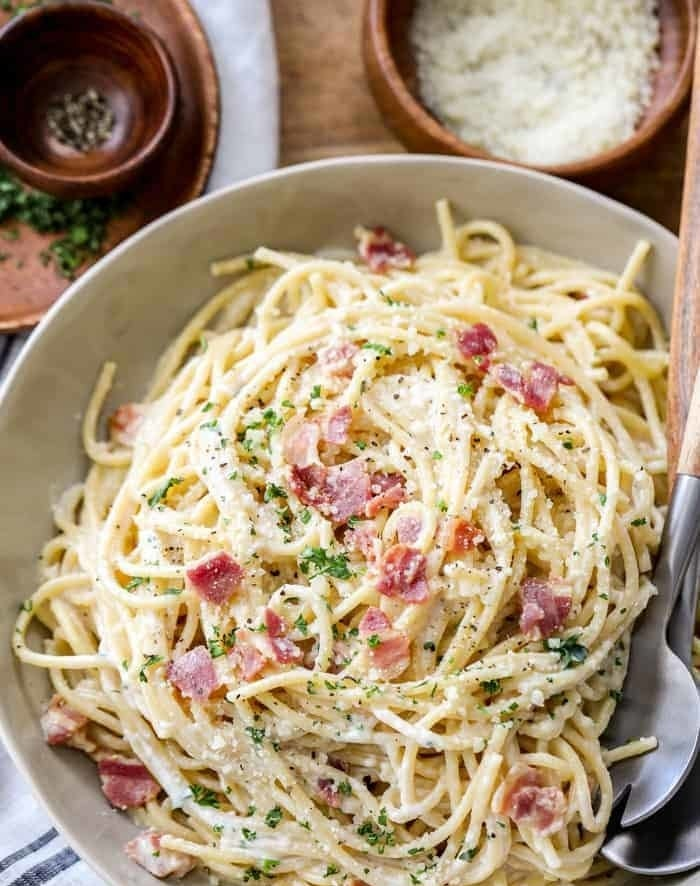 A plate of spaghetti carbonara with bacon and parsley.