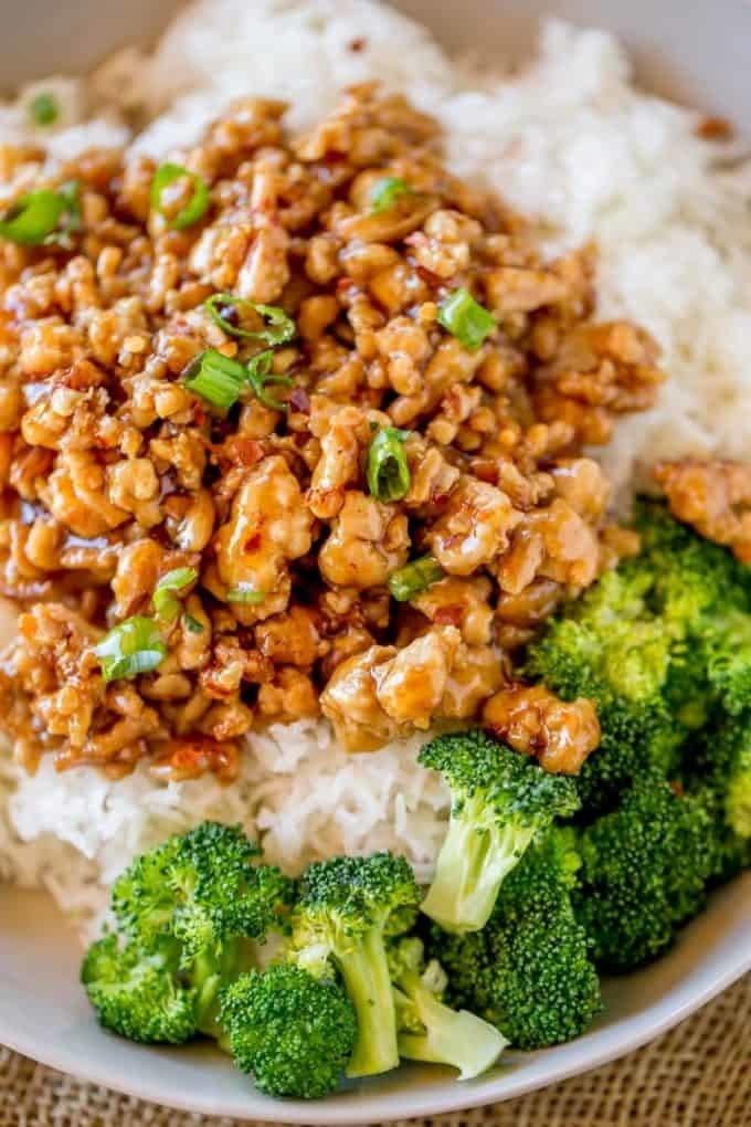 Ground orange chicken over rice with broccoli.