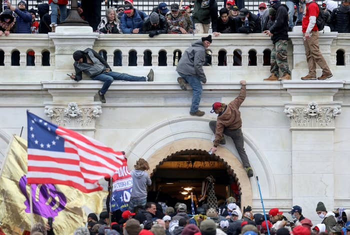 A mob of Trump supporters fight with members of law enforcement and scale walls of the Capitol