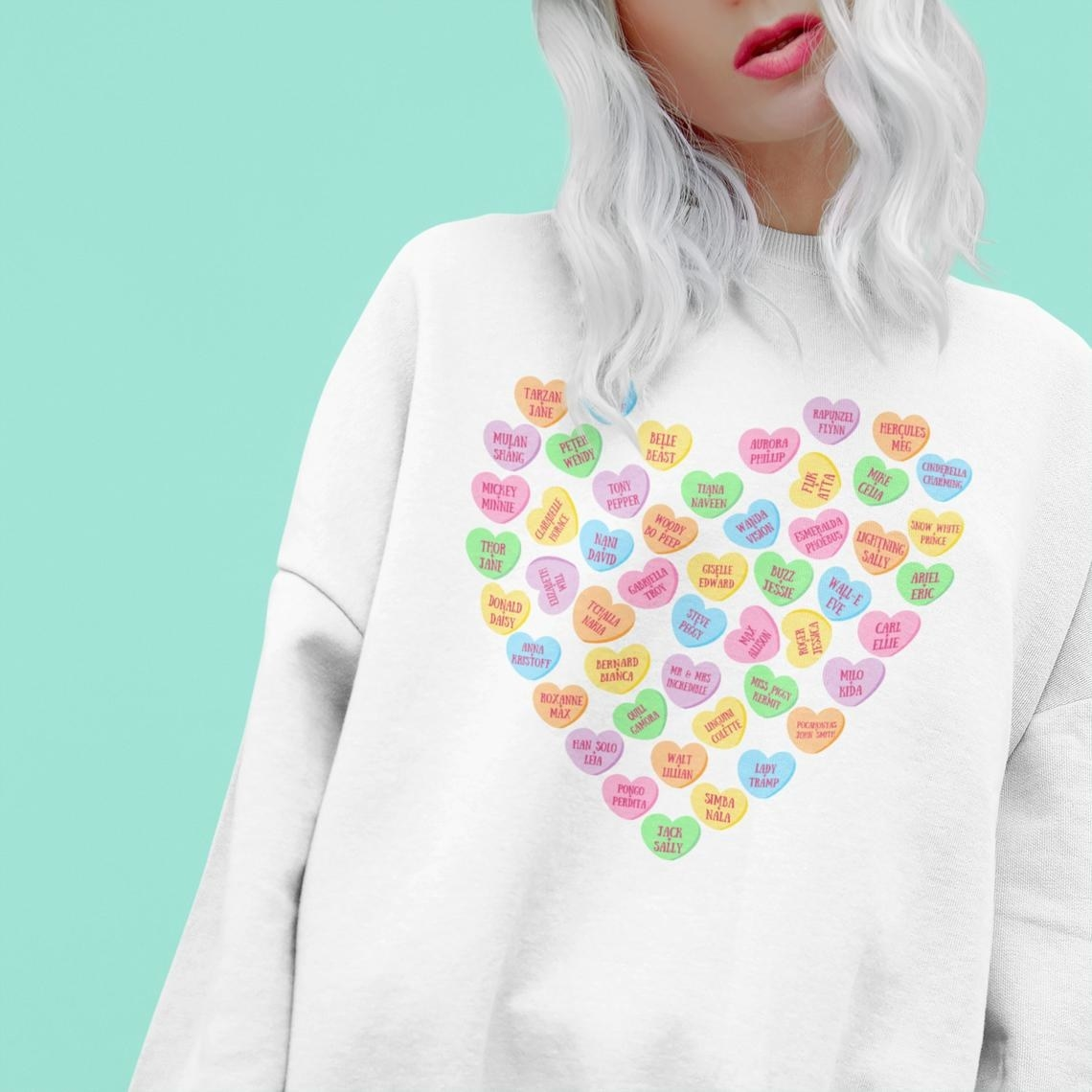 White sweatshirt with several candy hearts in the shape of a heart, each with the name of a different Disney couple