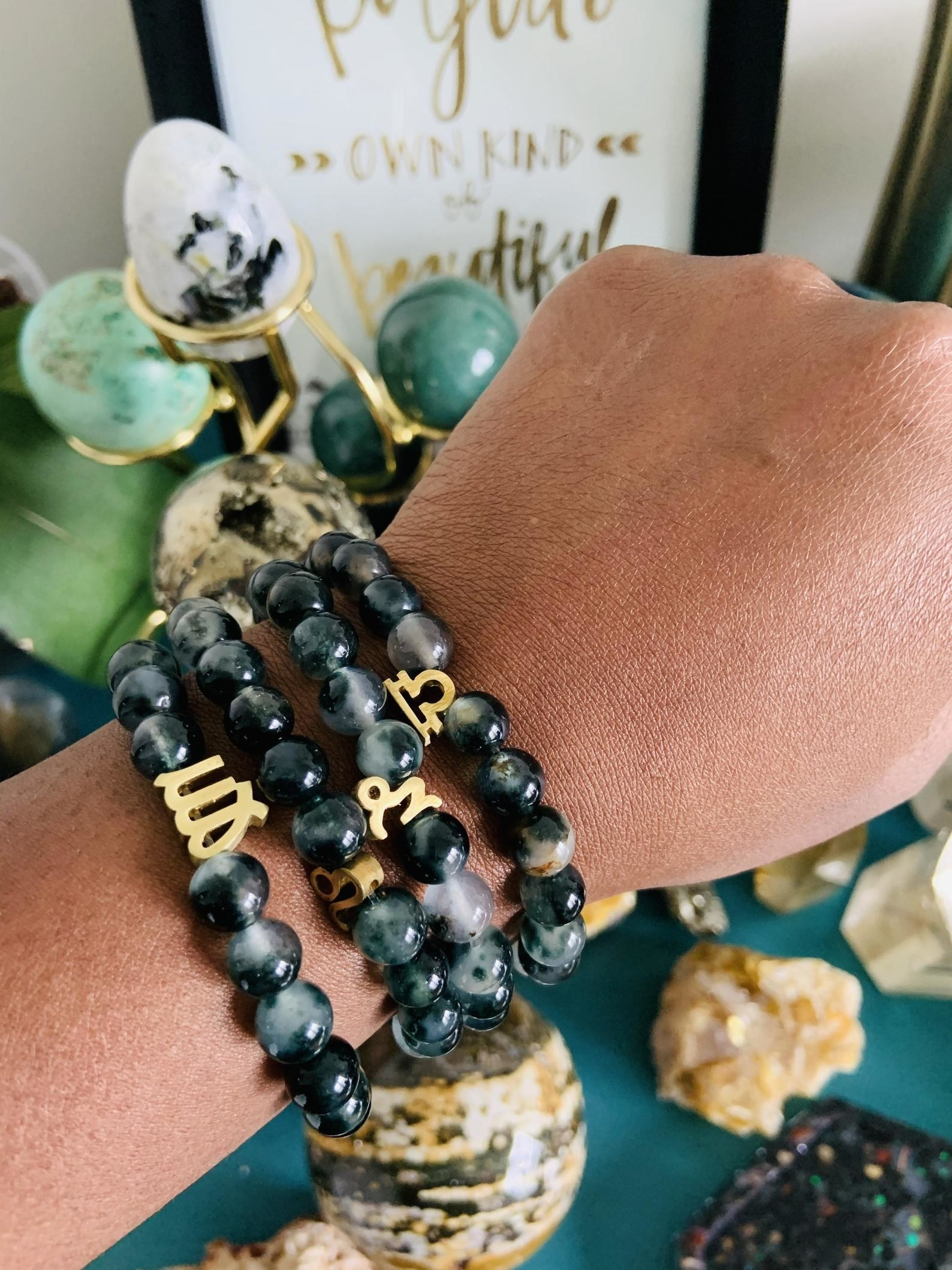 a model wearing a stack of gray marbled beaded bracelets with gold horoscope sign charms on each one