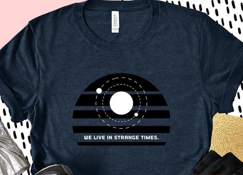 A t-shirt with a solar system and the words we live in strange times written on it