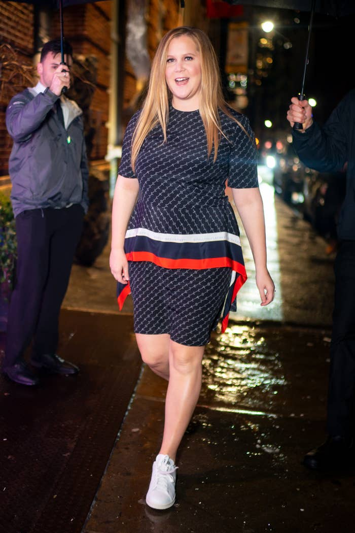 Amy Schumer walks through the rain as she attends the Stella McCartney holiday party in SoHo, New York wearing a short-sleeved dress and sneakers