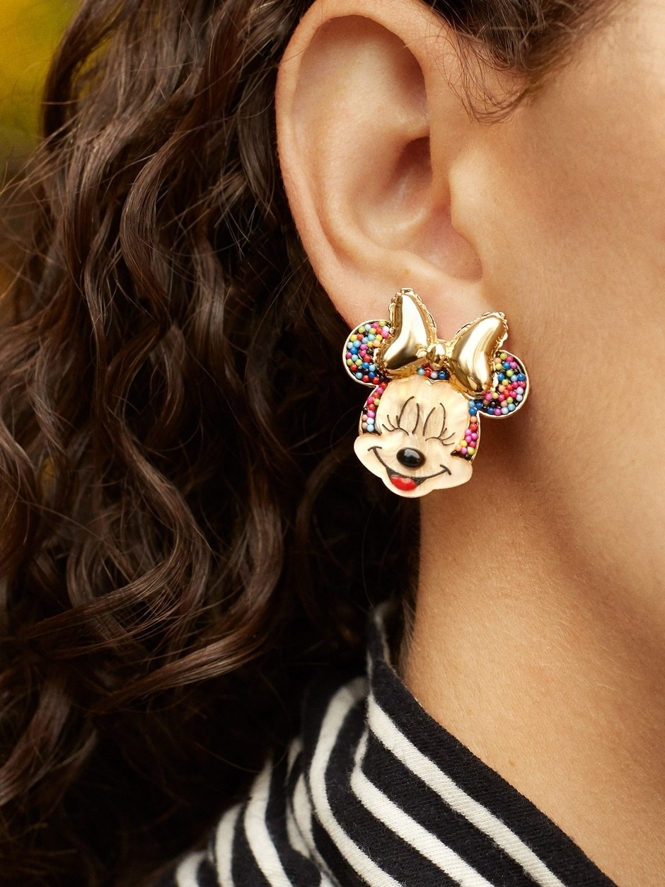 a model wearing minnie mouse earrings that look like they are filled with sprinkles