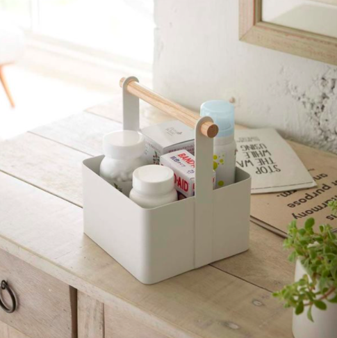 A sleek storage caddy with a wooden handle on a wooden counter