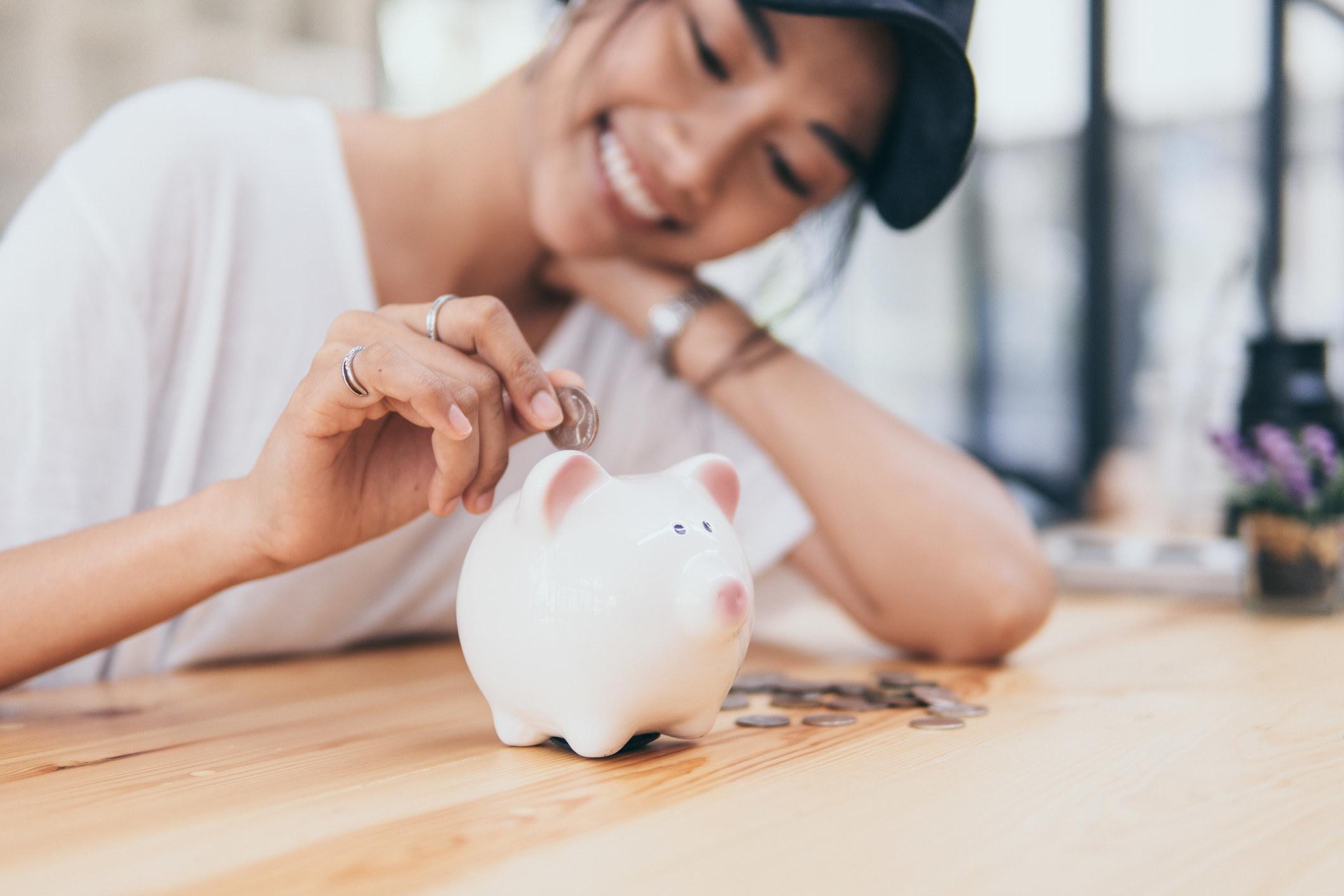 Model putting money into a piggy bank
