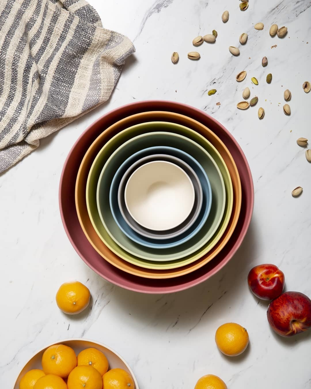 A flatlay of the bowls nested into each other on a marble counter surrounded by fruit