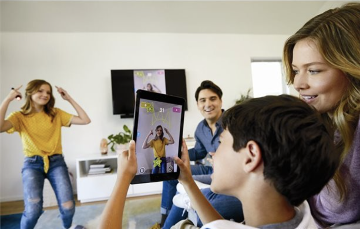 person drawing a crown and child using screen to see it