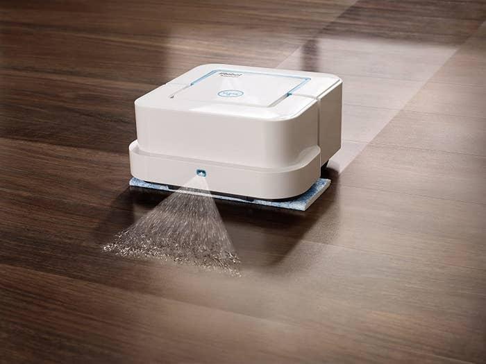 IRobot robotic mop spraying cleaning solution on hardwood floor