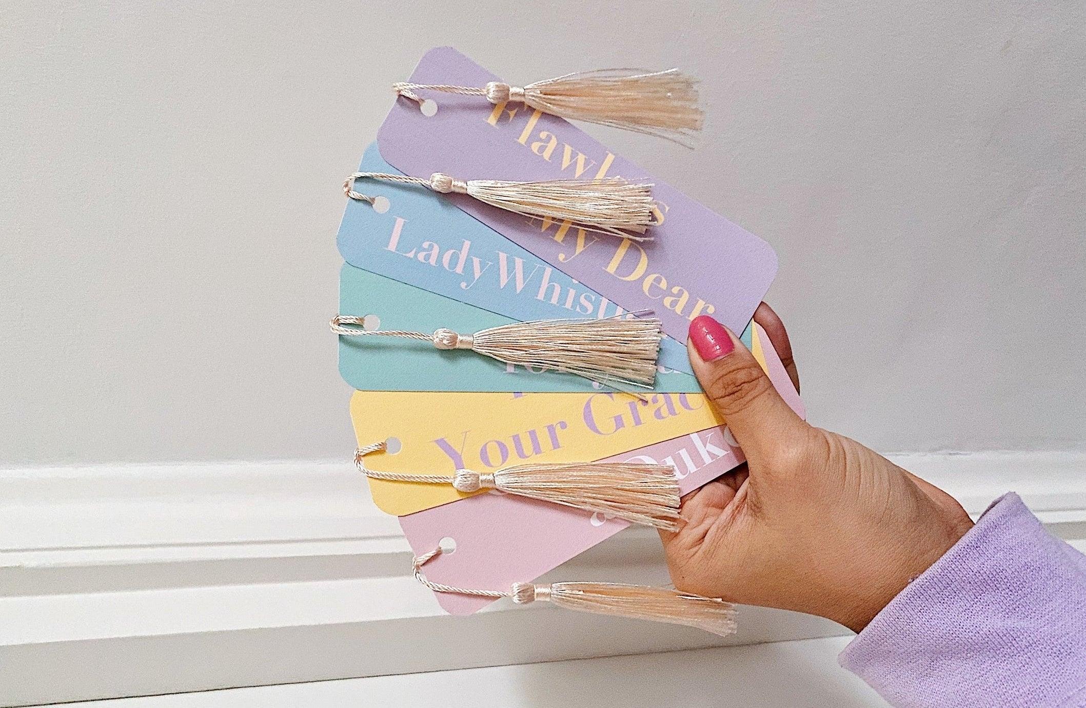 a person holding the five different pastel Bridgerton bookmarks