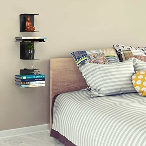 Shelves stacked with books and other items on a wall beside a bed.