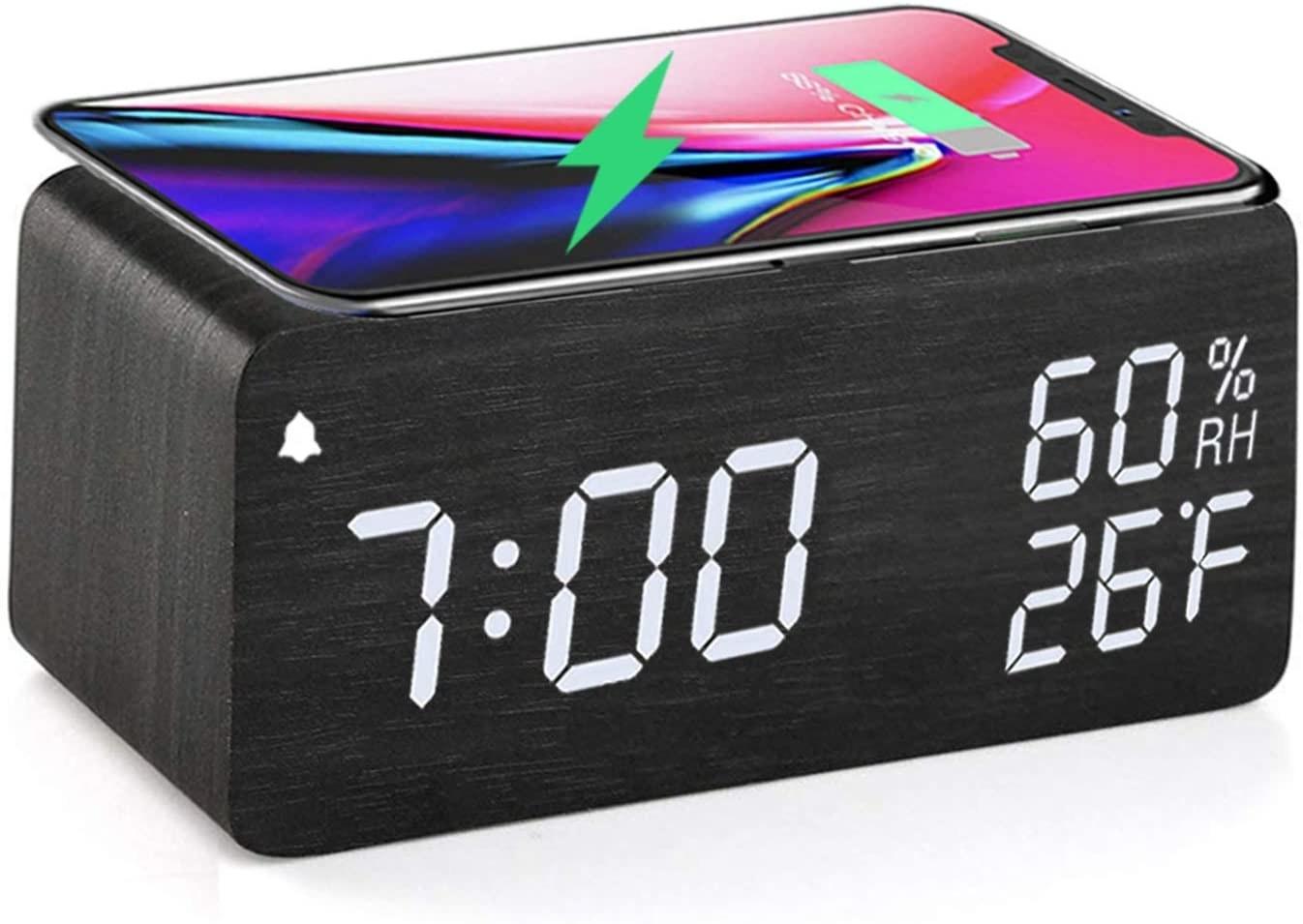 Smartphone wirelessly charging on top of alarm clock
