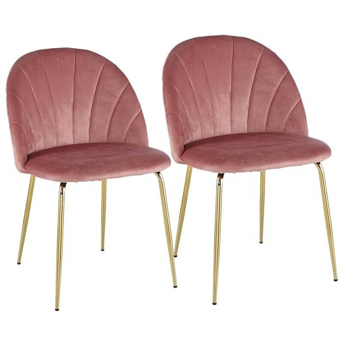 Two rose pink velvet chairs with rounded backs, scalloped seams, and gold legs