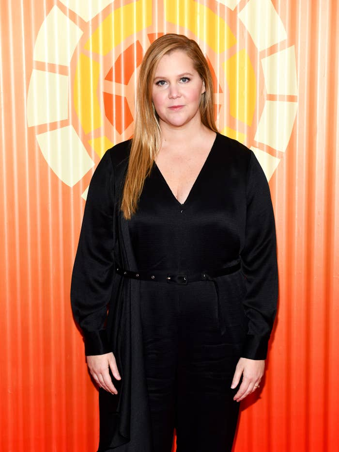 Amy Schumer attends Charlize Theron's Africa Outreach Project Fundraiser at The Africa Center in New York City and poses while wearing a belted jumpsuit