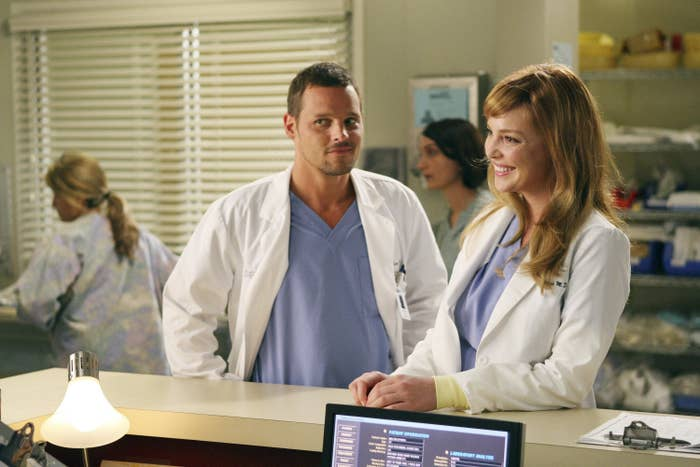Justin Chambers, wearing a white lab coat and a blue shirt, stands with his hands on his shoulders next to Katherine Heigl, leaning on a counter while wearing the same, in Grey's Anatomy
