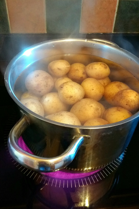 A pot of potatoes in broth on the stove