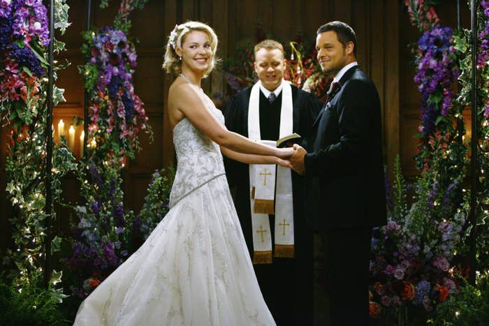 Heigl, in a white wedding dress, and Chambers, in a tuxedo, stand in front of a priest at the altar on Grey's Anatomy