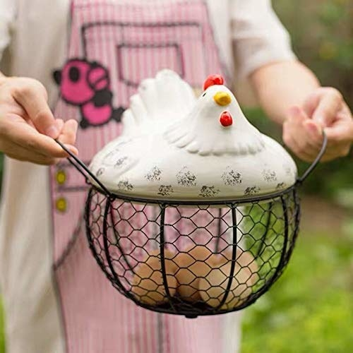 A person holding the rooster egg basket with eggs inside.