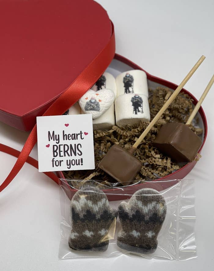 "Red heart-shaped box with hot cocoa sticks on a stick, marshmallows with pictures of Bernie Sanders on them, marshmallows that look like mittens, and a card that says ""My heart BERNS for you!"""