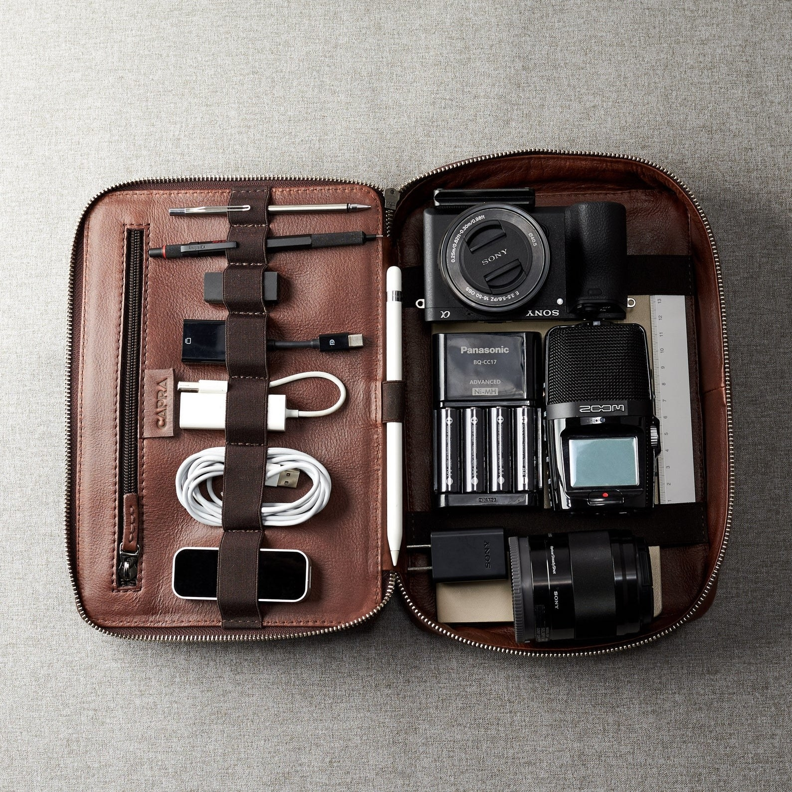 brown leather travel organizer used to store tech accessories