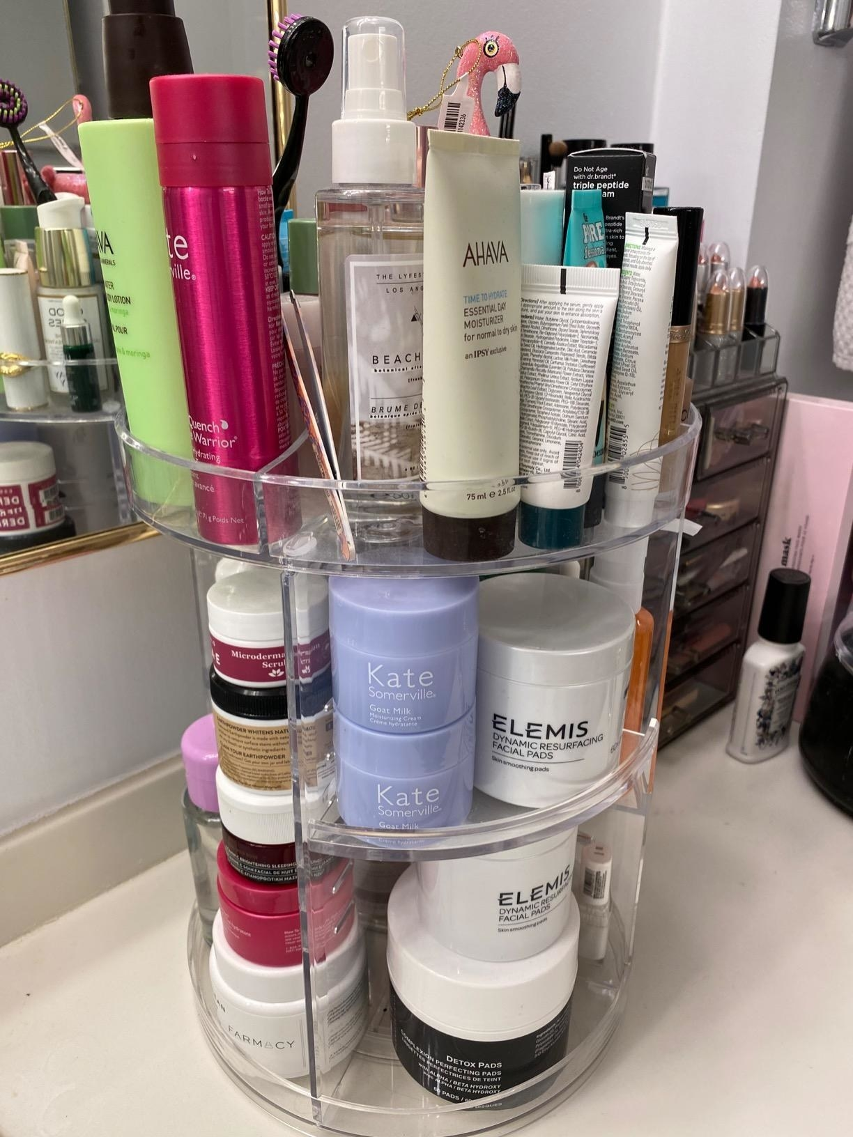 A reviewer's photo of the three-tier rotating organizer holding various skin, face, and hair products