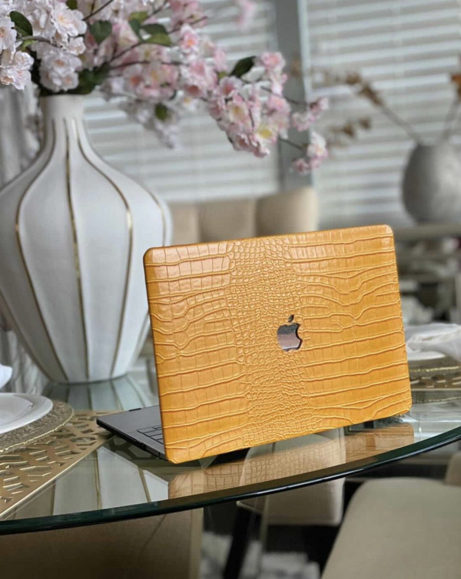 A golden yellow faux crocodile laptop case on a Macbook