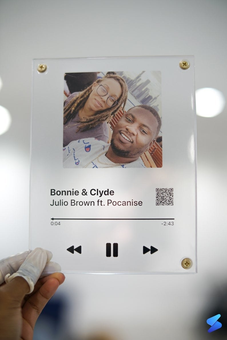 The clear plaque printed to look like the display of a phone screen while playing a song on a streaming service