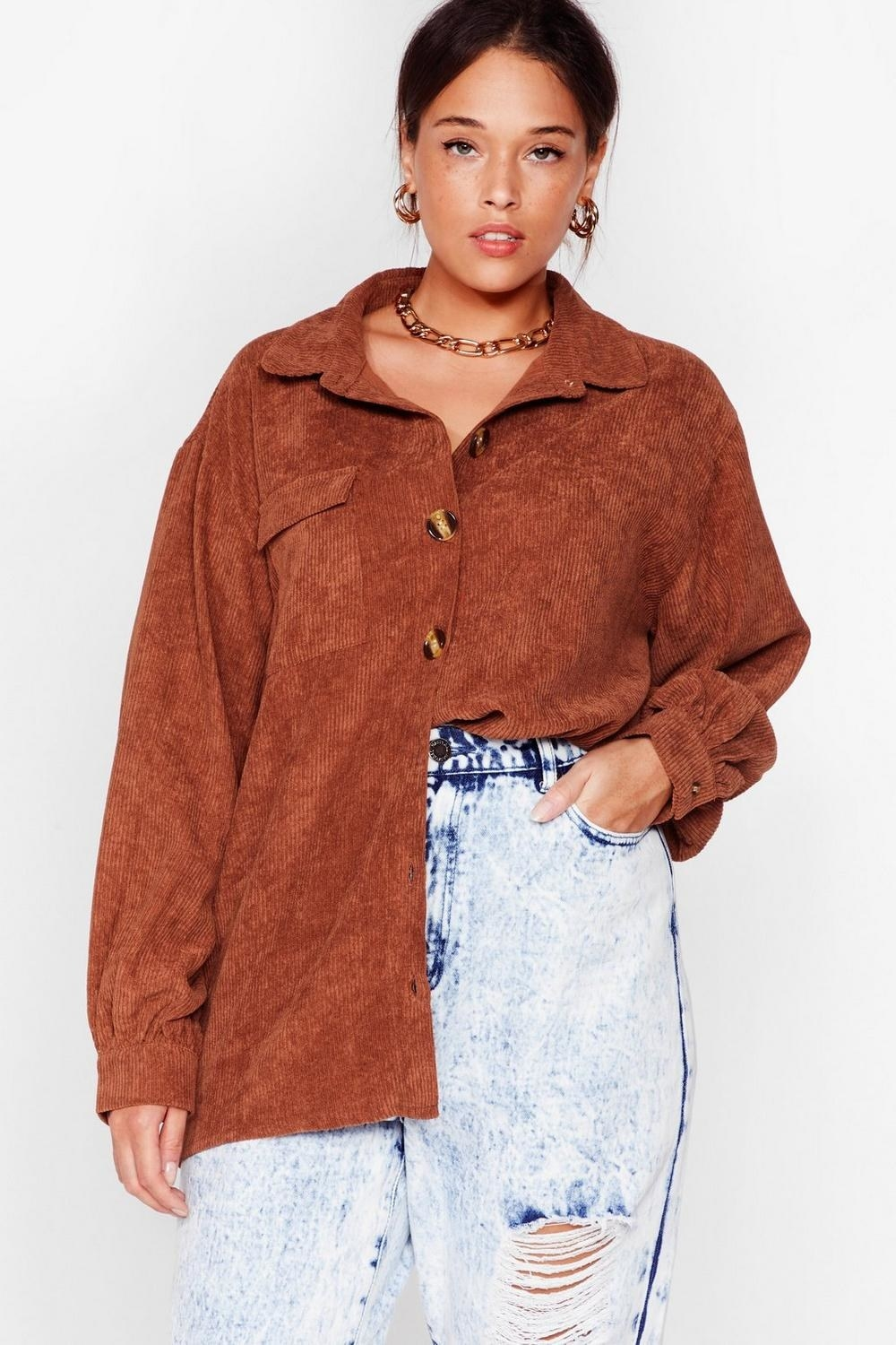 a model wearing the oversized button down top in the color brown