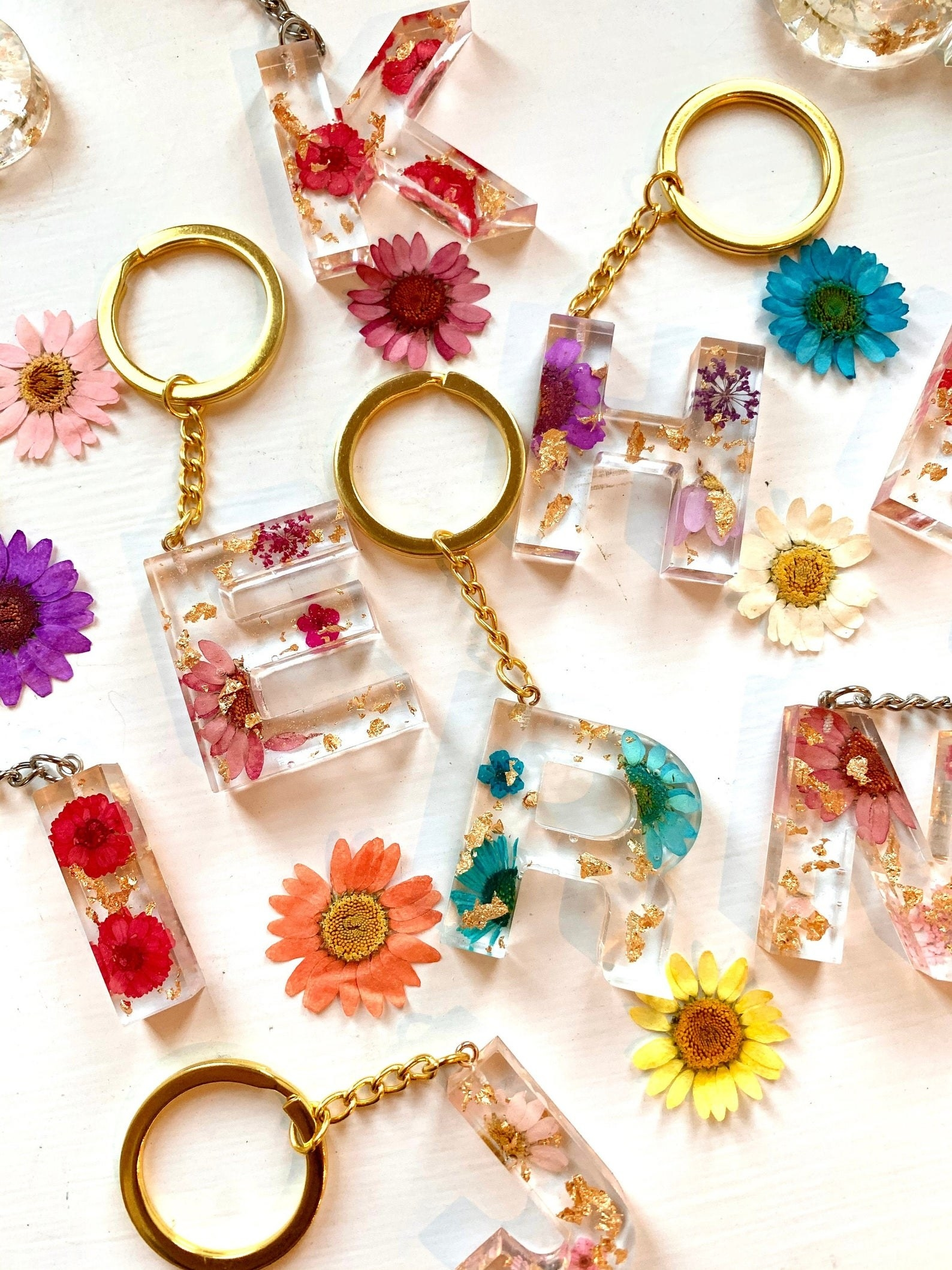 an assortment of floral resin letter keychains