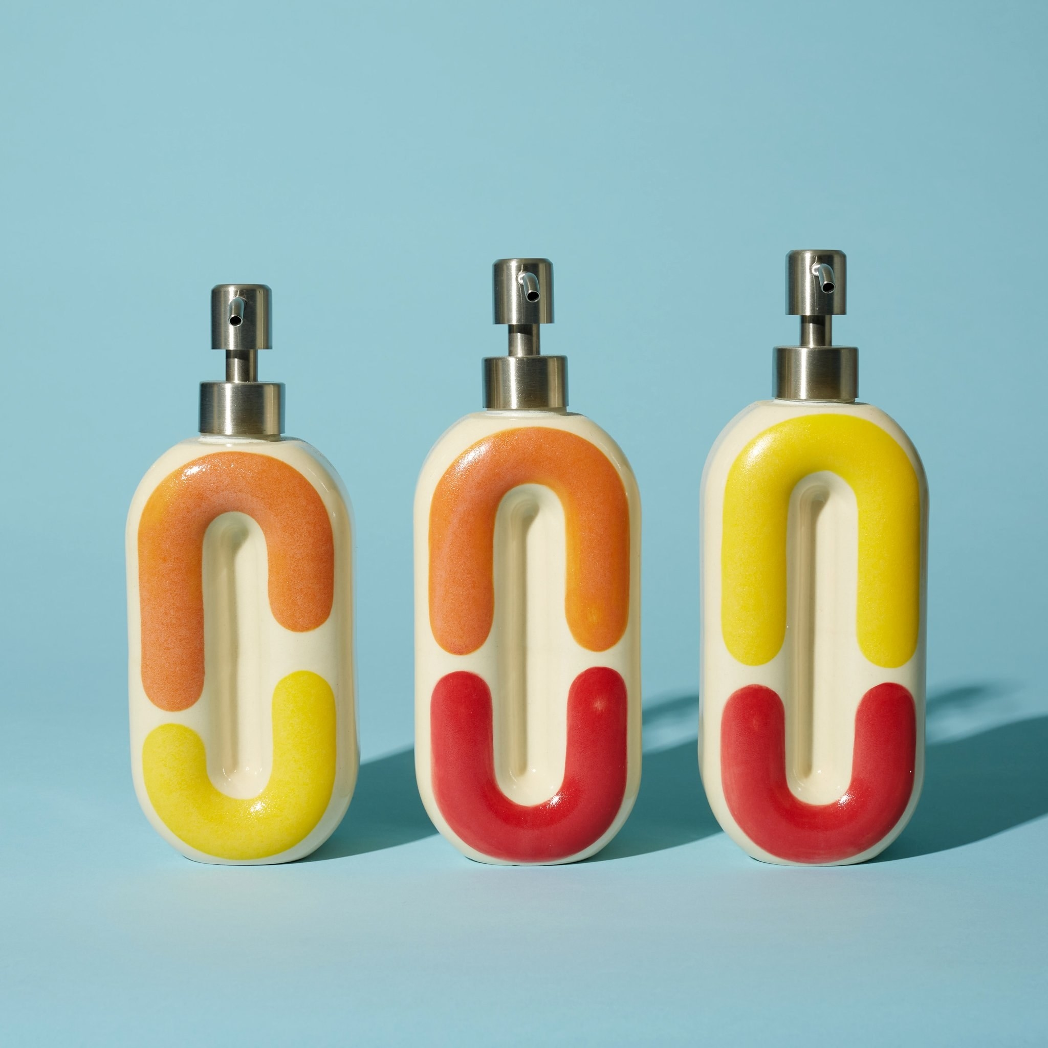 three pump bottles with squiggle designs in various combinations of red, yellow, and orange