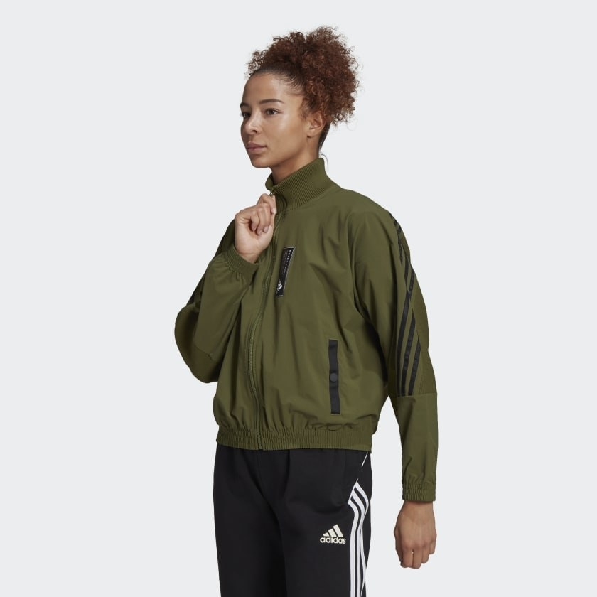 Model in a green high neck bomber jacket with black detailing on zippers and sleeves