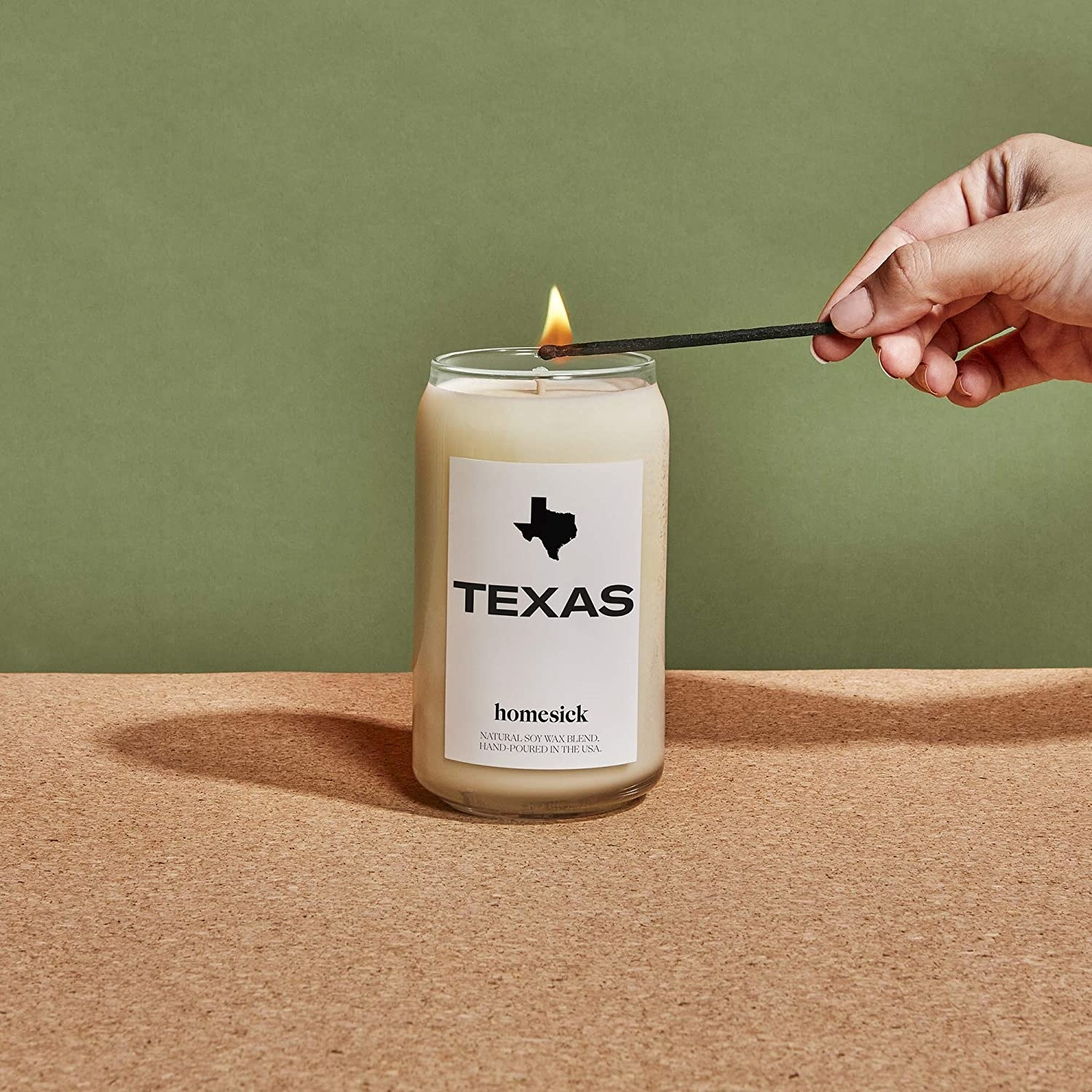 """a model lighting a cylinder candle that says """"texas"""" on it"""