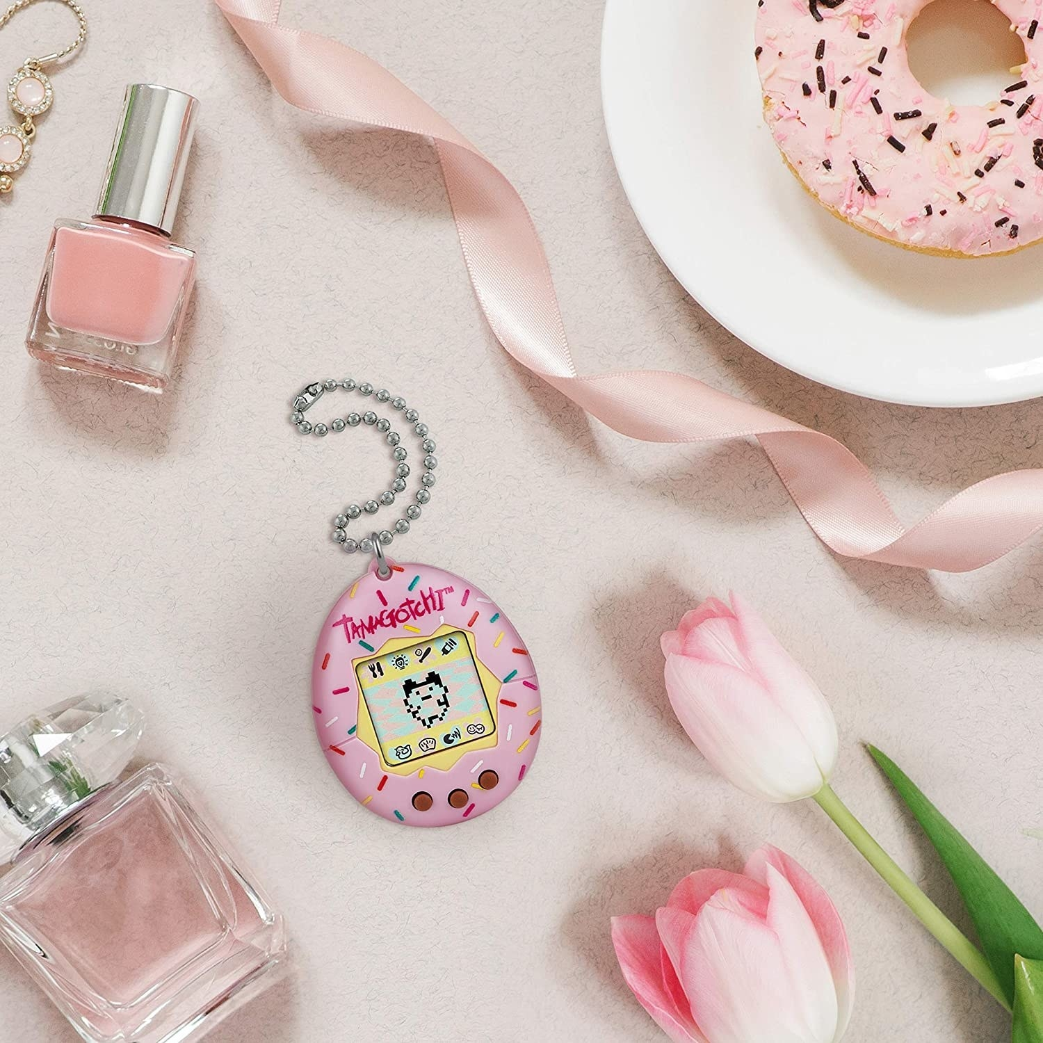 the tamagotchi surrounded by flowers, nail polish, perfume, and a donut