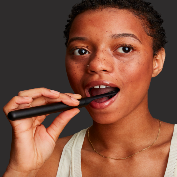 A person brushing their teeth with the Quip brush