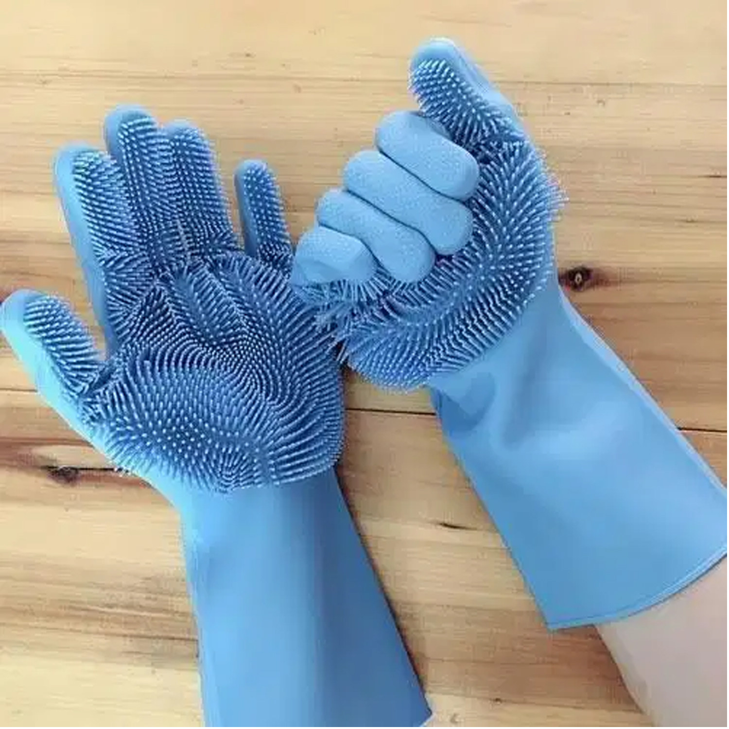 the blue reusable silicone dishwashing gloves on a model's hands