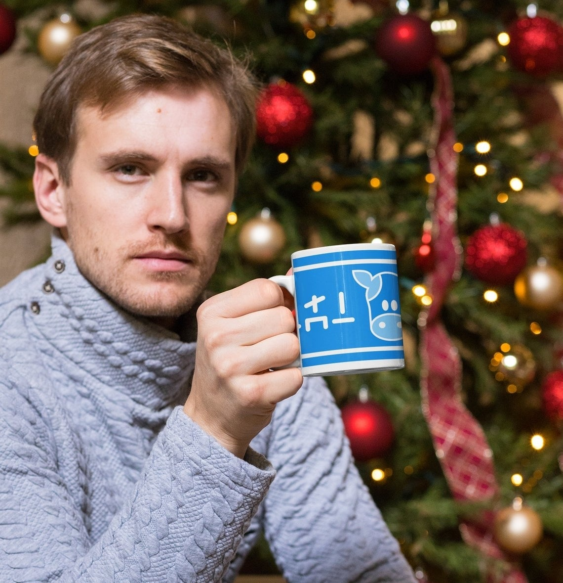 model drinks from mug with blue cow label on it