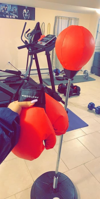 Reviewer holds red gloves in front of red and silver punching bag stand in home gym