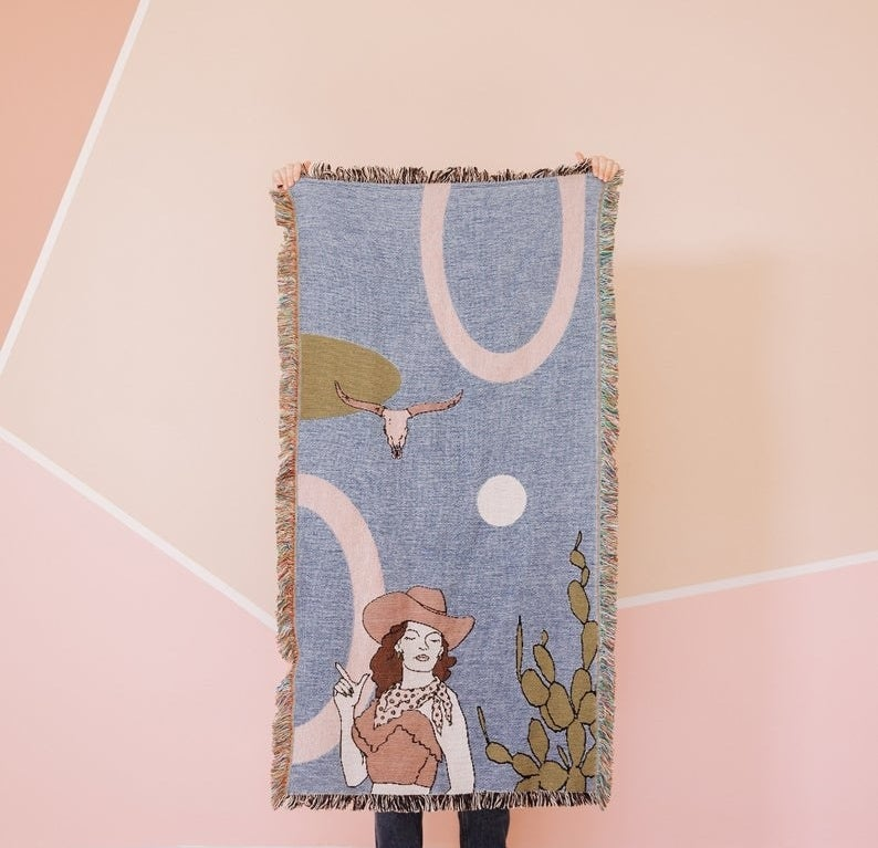 blanket with a cowgirl and cow skull in a pastel color palette