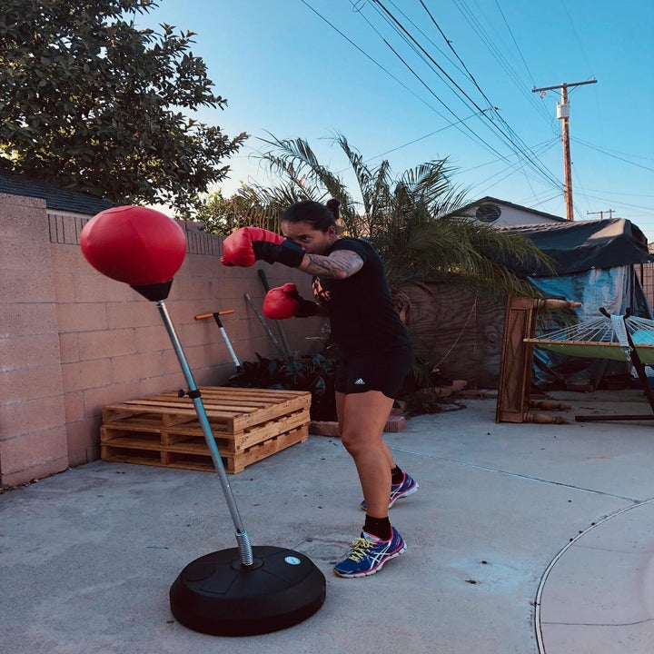 Reviewer wears red gloves and uses same punching bag to workout outdoors